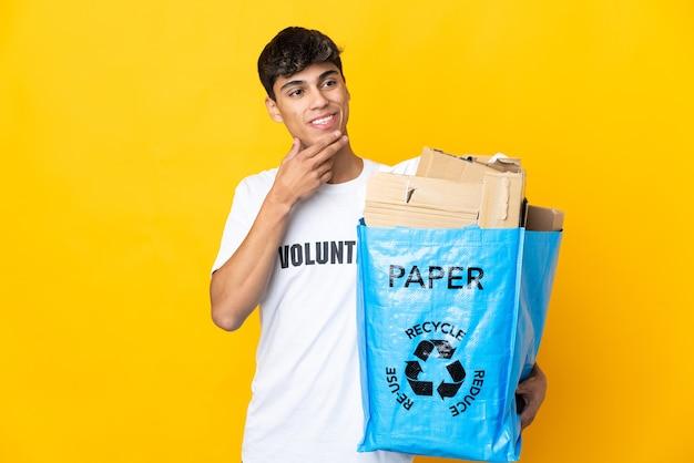 Man met een recyclingzak vol papier om te recyclen over geïsoleerde gele muur opzoeken terwijl lachend