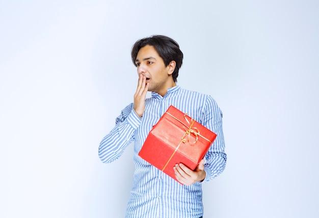 Man met een rode geschenkdoos ziet er bang en doodsbang uit. hoge kwaliteit foto