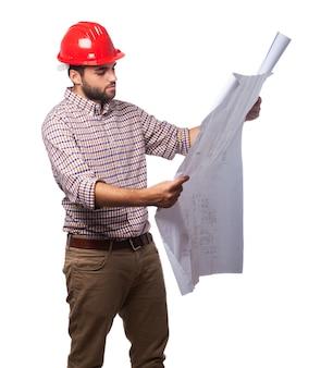 Man met een rode helm en op zoek blauwdrukken