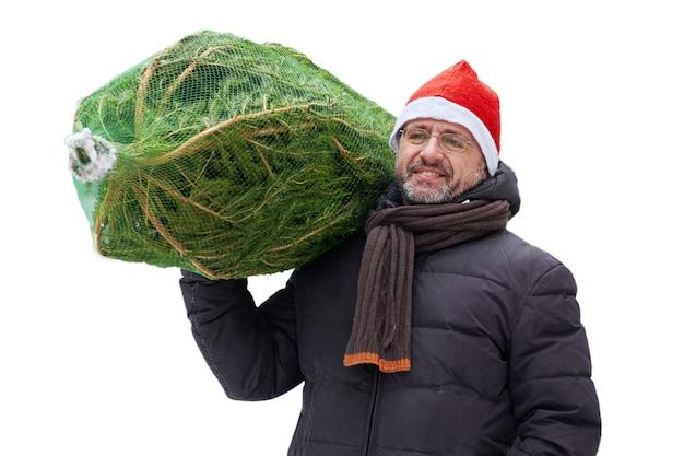 Man met een rode kerstmuts draagt een kerstboom verpakt in een raster