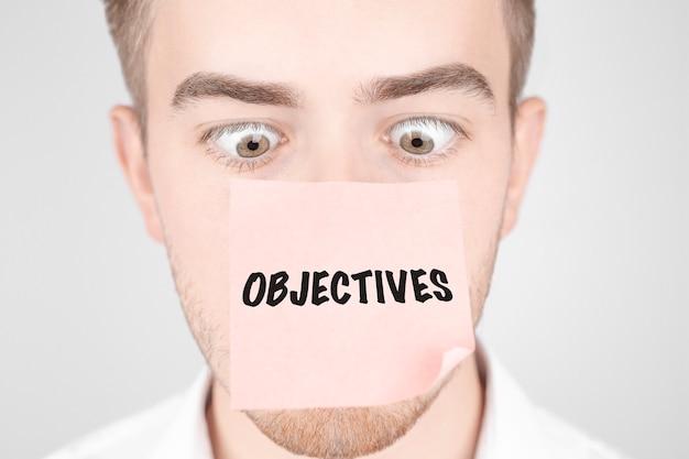 Man met een rode sticker op zijn neus leest de tekst objectives