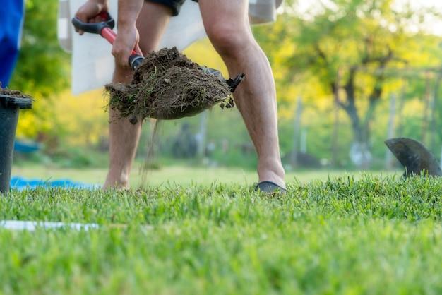 Man met een schop die in de tuin in de zomer werkt.
