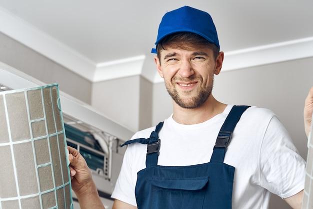 Man met een splitsysteem in zijn hand die een airconditioning binnenshuis repareert
