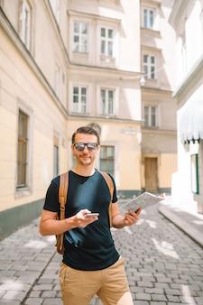 Man met een stadskaart en rugzak in europese straat.