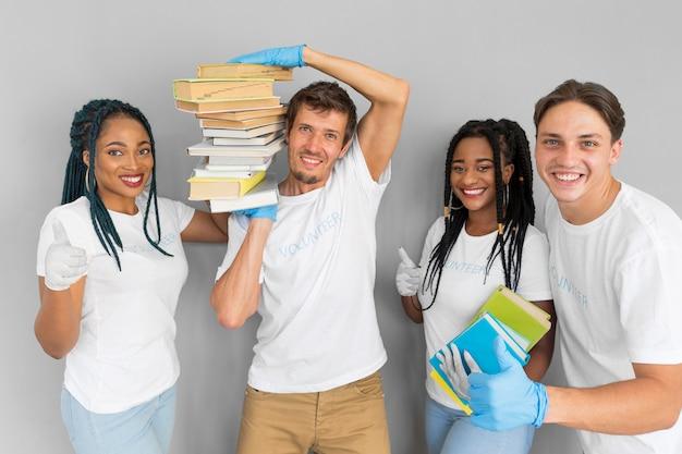 Man met een stapel boeken op zijn schouders naast zijn vrienden