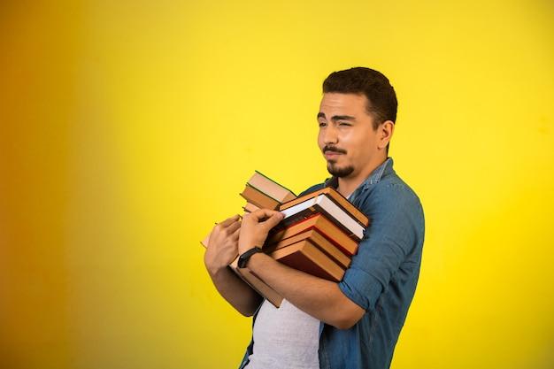 Man met een stapel zware boeken met twee handen en lachend.