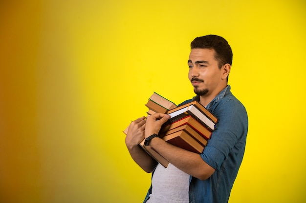 Man met een stapel zware boeken met twee handen en trots op zoek.