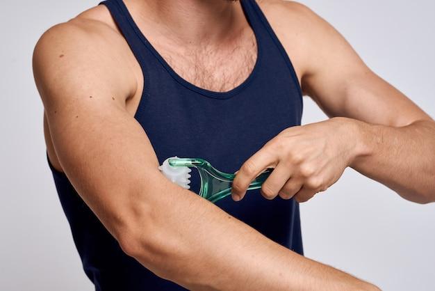 Man met een stimulator in zijn hand en in een blauw t-shirt spa-behandelingen hygiëne schone huid