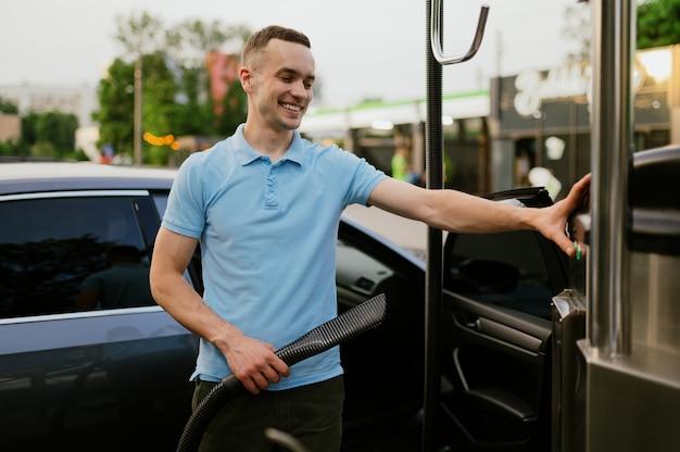 Man met een stofzuiger, autowasstation met de hand