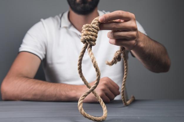 Man met een strop. zelfmoord concept. op grijze muur