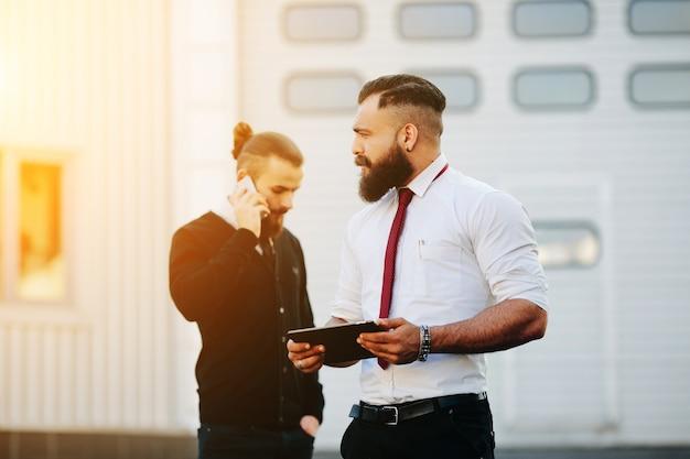 Man met een tablet, terwijl de andere spreekt op de telefoon