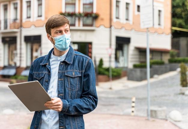 Man met een tablet terwijl hij een medisch masker met kopie ruimte draagt