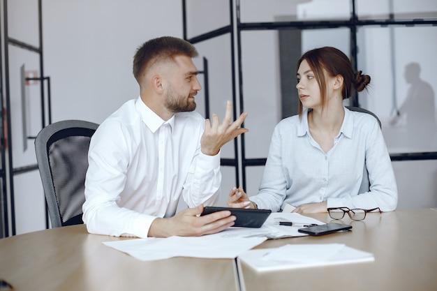 Man met een tablet. zakelijke partners op een zakelijke bijeenkomst. mensen zitten aan de tafel