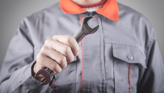 Man met een uniform met een moersleutel.