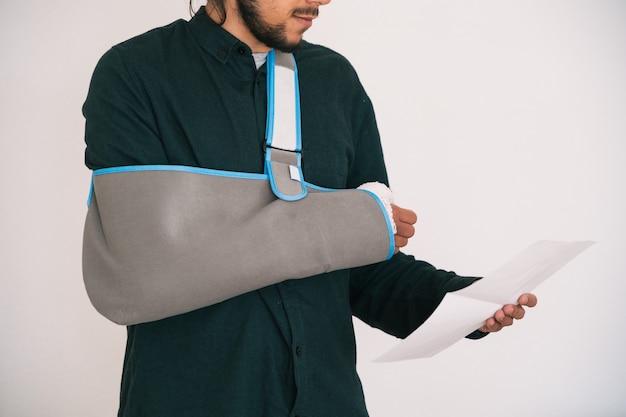 Man met een verbonden arm vastgehouden door een textielen slinger die zijn arm vasthoudt en een krant leest