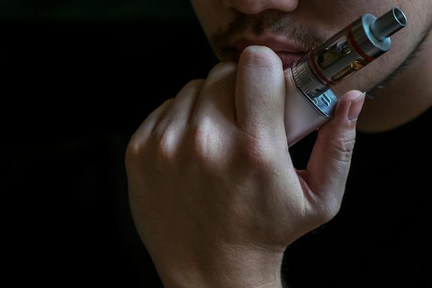 Man met een verborgen identiteit die een controversiële vaping van een elektronische sigaret rookt. vaping is debatbaar in de gezondheidsgemeenschap als het veilig of een gezondheidsrisico is