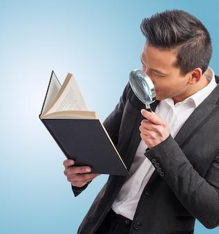Man met een vergroot glas op zoek naar een boek