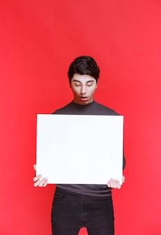Man met een vierkant denkbord om te gamen