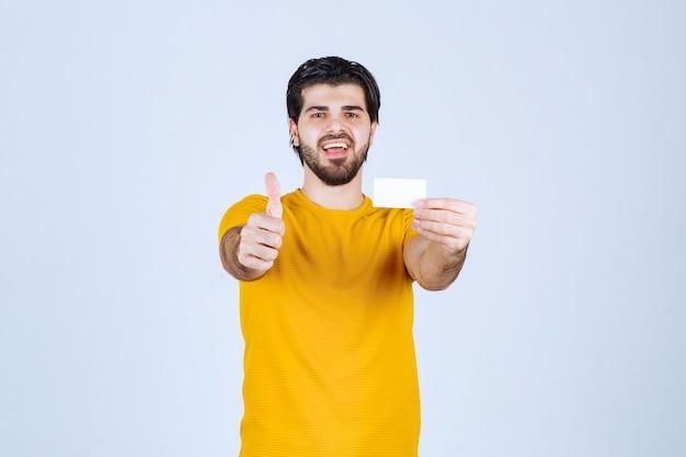 Man met een visitekaartje en duim opdagen.