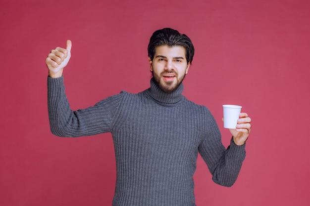Man met een wegwerp koffiekopje en plezier teken maakt.