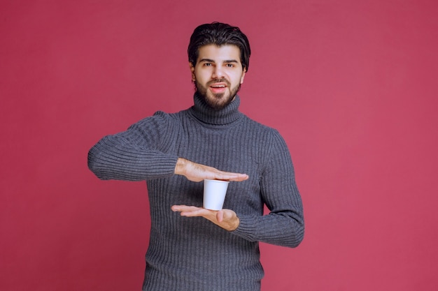 Man met een wegwerp koffiekopje in de hand en voelt zich positief.