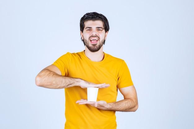 Man met een wegwerp koffiekopje tussen handen.