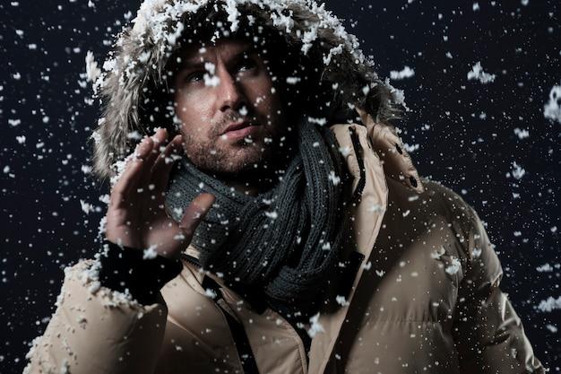 Man met een winterjas terwijl het sneeuwt