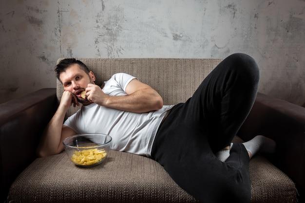 Man met een wit shirt ligt op de bank, eet chips en kijkt naar een sportkanaal.