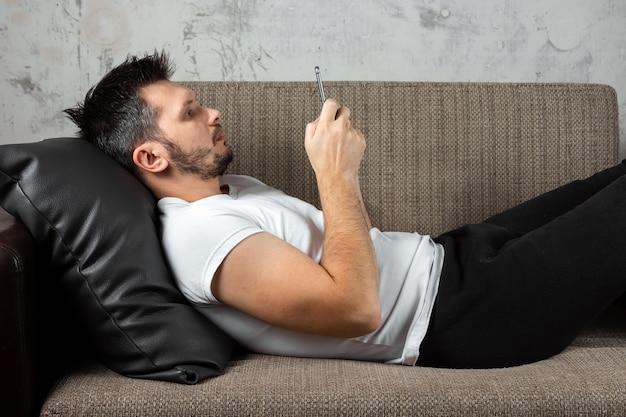 Man met een wit shirt ligt op de bank en zit in de telefoon.