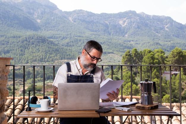 Man met een witte baard zit met een laptop op het terras in een groot raam