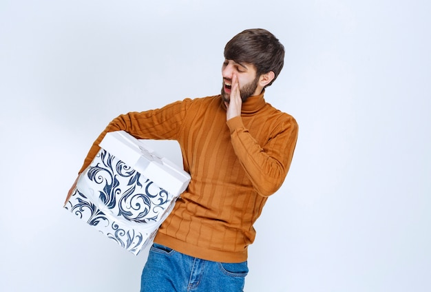 Man met een witte geschenkdoos met blauwe patronen die geluid maakt om iemand op te merken.