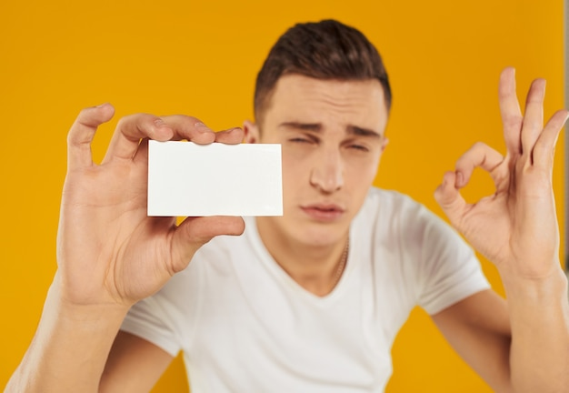 Man met een witte kaart op een gele achtergrond