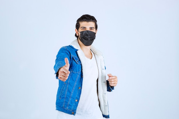 Man met een zwart masker dat een teken van plezier toont en zich goed voelt.