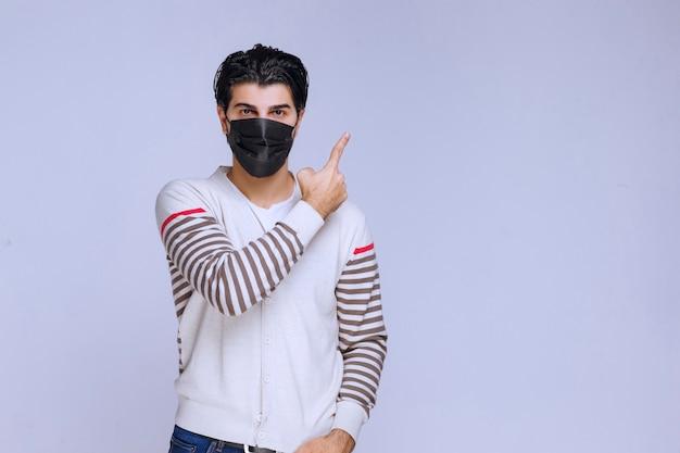 Man met een zwart masker dat ergens naar wijst.