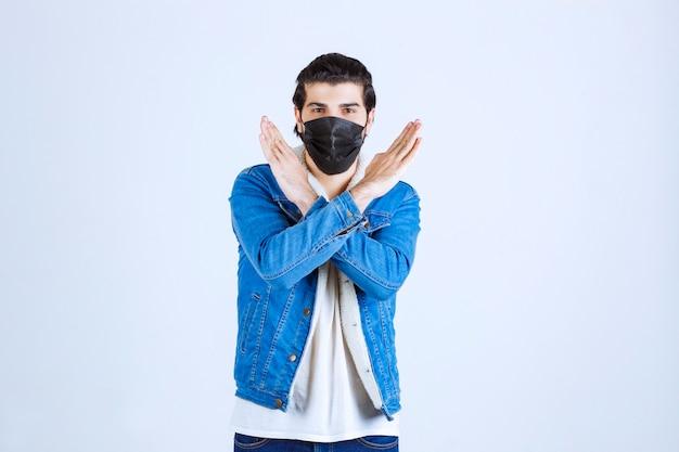 Man met een zwart masker die een stopteken geeft aan het virus.