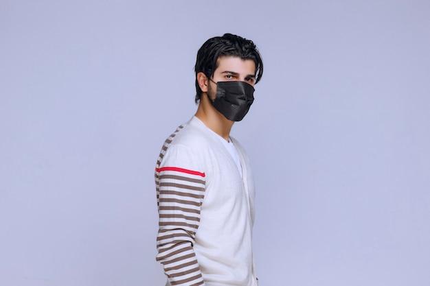 Man met een zwart masker om covid te voorkomen.