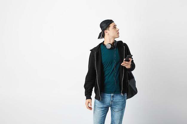 Man met een zwarte rugzak gebruikt mobiele telefoon