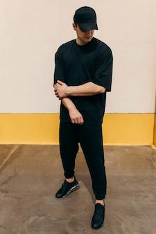 Man met een zwarte t-shirt en een zwarte baseballpet met op een muur in de buitenlucht