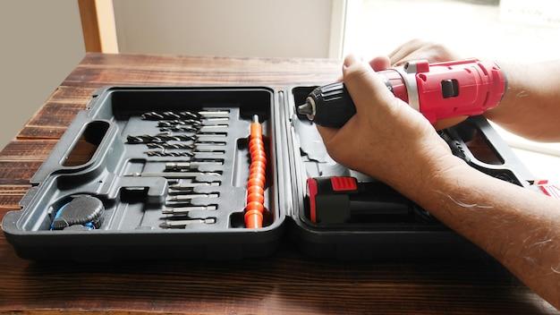 Man met elektrische handboor in de hand met boor in diy box set