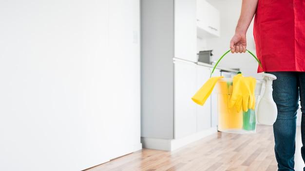 Man met emmer schoonmaakproducten