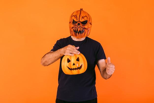 Man met eng pompoenlatexmasker met blauw t-shirt, houdt een 'jack-o-lantern'-pompoen en duimen omhoog, op oranje achtergrond. halloween en dagen van het dode concept.