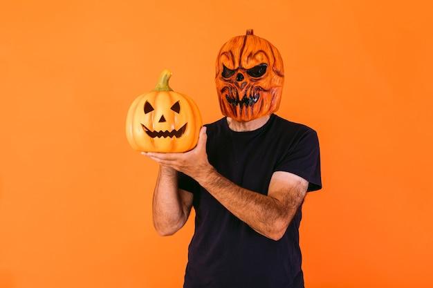 Man met eng pompoenlatexmasker met blauw t-shirt, met 'jack-o-lantern'-pompoen op oranje achtergrond. halloween en dagen van het dode concept.