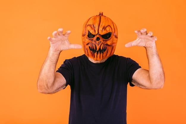 Man met eng pompoenlatexmasker met blauw t-shirt schrikt met zijn handen, op oranje achtergrond. halloween en dagen van het dode concept.
