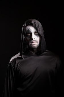 Man met enge make-up voor halloween met een capuchon geïsoleerd op zwarte achtergrond.