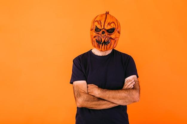 Man met enge pompoen latex masker met blauw t-shirt met gekruiste armen, op oranje achtergrond. halloween en dagen van het dode concept.