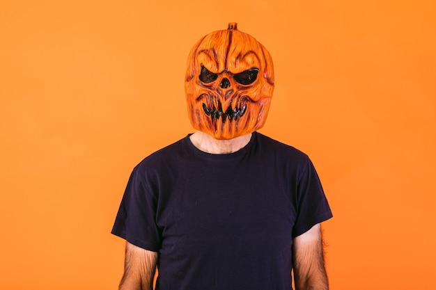 Man met enge pompoen latex masker met blauw t-shirt op oranje achtergrond. halloween en dagen van het dode concept.