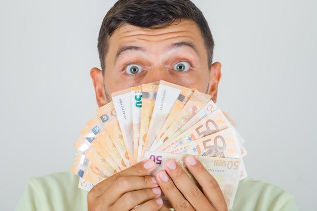 Man met eurobankbiljetten in t-shirt en geschokt op zoek.