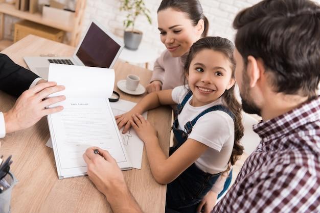 Man met familie tekent een koopcontract met een zelfverzekerde makelaar