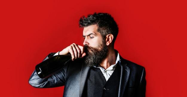 Man met fles met champagne, wijn. de persoon houdt een fles rode wijn in een hand. bebaarde man met een fles champagne van en glas. stijlvolle man in smoking, pak, jas.