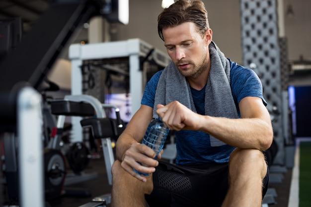 Man met fles water op sportschool
